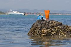 Mask and sun lotion. A diving mask and a tube of sun lotion at the edge of the sea Stock Photography