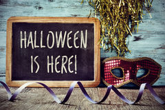 Mask and text Halloween is here in a chalkboard Royalty Free Stock Image