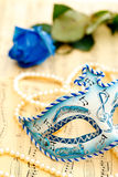 Mask from Venice. Beautiful mask from Venice on a music paper with blue rose and white pearl Stock Images