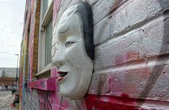 Street art. Mask on wall. Mask on a wall street art in the East End of London, UK. Culturally and artistically diverse area of the capital stock photo