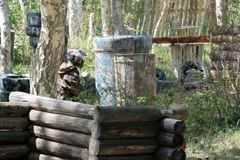 Mask, weapons, camouflage from the player during the game of paintball. Waiting for the enemy in ambush. Tires, barrels. Mask, weapons, camouflage from the Stock Photos
