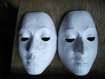 Mask. The white mask is also unfinished on a wooden desk Royalty Free Stock Photo