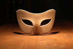 Mask On Wood. White venetian mask lying on wooden surface with lighting effect