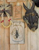 Mask and wooden pictures. Black devil mask and wooden pictures with bugs hanging on wall , Lithuania Stock Photo