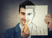 Mask your emotion. Portrait of a smiling businessman hiding half face with a white empty paper, drawing his real angry emotion. Create new identity, grey wall stock images