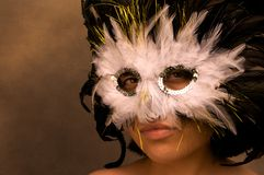 Masked. Color photograph of a young woman wearing a Mardi Gras mask