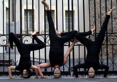 Masked actors upside down. AURILLAC, FRANCE - AUGUST 23: actors upside down in the street as part of the Aurillac International Street Theater Festival, show La Stock Photography