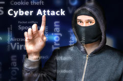 Masked anonymous hacker is pointing on Cyber attack.  Stock Image