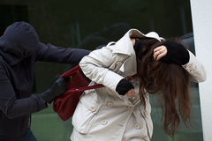 Masked attack. A masked thief attacking an innocent woman in the street Royalty Free Stock Image