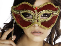 Masked beauty. Beautiful mysterious woman's face behind ornate red and gold mask