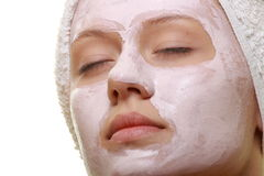 Masked Beauty - facial treatment. Portrait of a styled model with facial cream mask Stock Photos
