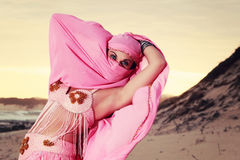 Masked Belly dancer performing on the beach Royalty Free Stock Images
