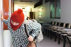 Masked burglar with bags entering into house ready to commit crime.  royalty free stock photos