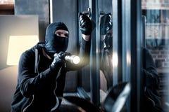 Masked burglar breaking into the house. Burglary. Skilful professional masked burglar opening a window and holding a torch and breaking into the house stock image
