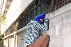 Masked burglar climbs through a fence. Catch burglar concept.  Stock Photos
