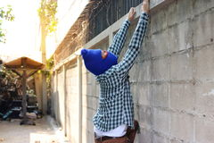 Masked burglar climbs through a fence. Catch burglar concept Stock Photo
