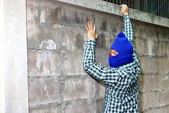 Masked burglar climbs through a fence. Catch burglar concept.  Royalty Free Stock Image