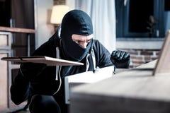 Masked burglar committing a crime. Crime. Dark-eyed skilful masked burglar wearing a uniform and holding a folder while committing a crime Stock Photo