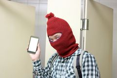 Masked burglar holding and showing mobile smart phone on his hands in toilet. Dangerous social crime concept. Masked burglar holding and showing mobile smart Royalty Free Stock Image