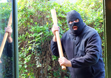 Masked burglar or robber attacking home. A robber or burglar wearing a mask and carrying a pick ax handle coming into a home through the door to attack and stock images
