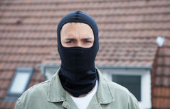 Masked burglar with roofs in the background Royalty Free Stock Photography