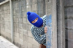 Masked burglar sneaking behind concrete pole before the burglary. Crime concept Royalty Free Stock Photo