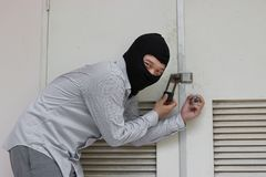 Masked burglar wearing a balaclava escaping after sneaking into the house. Crime concept.  stock image