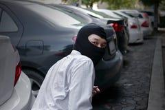 Masked burglar wearing a balaclava ready to burglary against car background. Insurance crime concept. Masked burglar wearing a balaclava ready to burglary stock photography