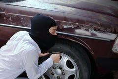 Masked burglar wearing a balaclava ready to burglary against car background. Insurance crime concept. Masked burglar wearing a balaclava ready to burglary stock photos