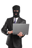 Masked businessman holding a laptop Royalty Free Stock Photo