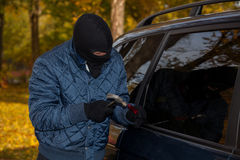 Masked car criminal. A masked criminal about to steal a car Royalty Free Stock Photos