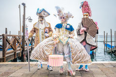 Masked carnival costumes trio Stock Photo