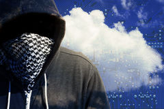 Masked Computer Hacker Thief Concept. Hooded and masked computer hacker thief with a cloud computer based background and tech backdrop. Unknown technology threat Royalty Free Stock Images