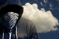 Masked Computer Hacker Thief Concept. Hooded and masked computer hacker thief with a cloud computer based background. Unknown technology threat to the cloud Royalty Free Stock Photo