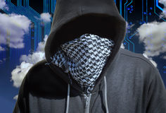 Masked Computer Hacker Thief Concept. Hooded and masked computer hacker thief with a cloud computer based background. Unknown technology threat to the cloud Royalty Free Stock Photos