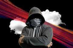 Masked Computer Hacker Thief Concept. Hooded and masked computer hacker thief with a cloud computer based background. Unknown technology threat to the cloud Royalty Free Stock Image