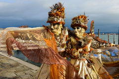 Masked couple in orange costumes Royalty Free Stock Photos