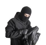 Masked criminal holding a stolen handbag Stock Image