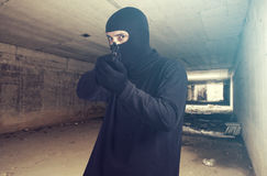 Masked criminal pointing a gun Royalty Free Stock Image
