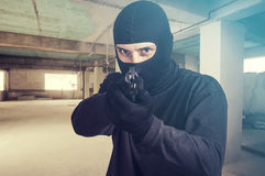 Masked criminal pointing a gun Royalty Free Stock Photo