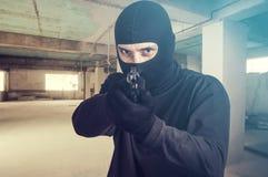 Masked criminal pointing a gun Royalty Free Stock Photo