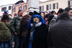 Masked face in crowd, Venice. Person wearing traditional mask and cloak in Venice Royalty Free Stock Photos