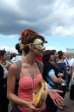 Masked female protester plays tambourine Royalty Free Stock Photography