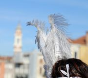 Masked girl with big feathers over rialto bridge in venice Royalty Free Stock Photos