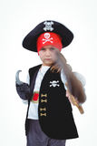 Masked girl pretending to be pirate. Masked girl wielding sword pretending to be pirate on white screen Stock Photo