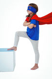 Masked girl pretending to be superhero. Masked girl with arms crossed and feet on white box on white screen pretending to be superhero Royalty Free Stock Photos
