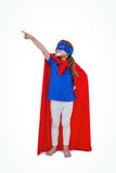 Masked girl pretending to be superhero. Masked girl pointing somewhere on white screen pretending to be superhero Royalty Free Stock Image