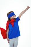 Masked girl pretending to be superhero. Raising fist on white screen Stock Images