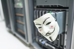 Masked Hacker in Computer Server room Concept . Stock Images