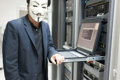 Masked Hacker in Computer Server room Concept . Stock Photography